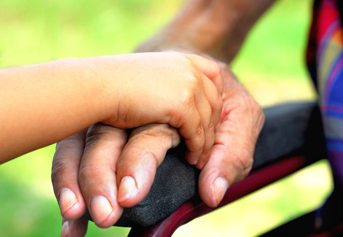 A child's hand resting on an older person's hand in a wheelchair