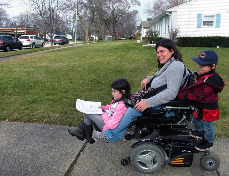 This is a photo of a woman who has cerebral palsy. She is in a motorized wheelchair. Her daughter is riding on the front on the chair and her son is standing on the back.