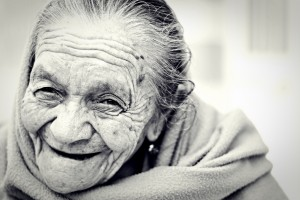 Black and white close up of an elder woman's face with gentle smile.