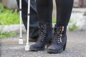 Feet of a woman wearing black boots with a cane