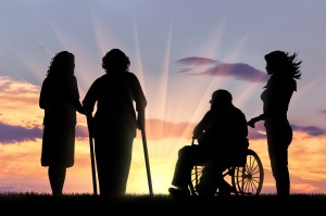 Silhouettes of people with disabilities looking at a dawn